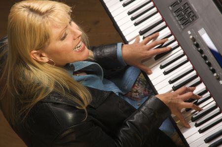 Femal Musician Sings While Playing Digital Piano photo