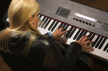 femal: Femal Musician Sings While Playing Digital Piano Stock Photo