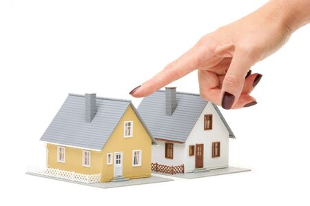 Female hand pointing at a house isolated on a white background. photo