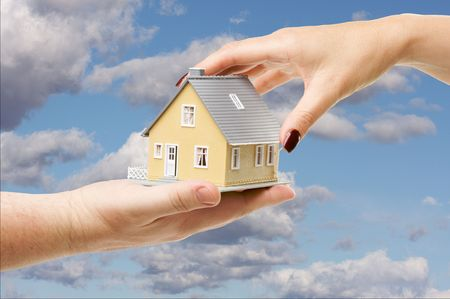 Female hand reaching for a house on a partly cloudy sky background. photo
