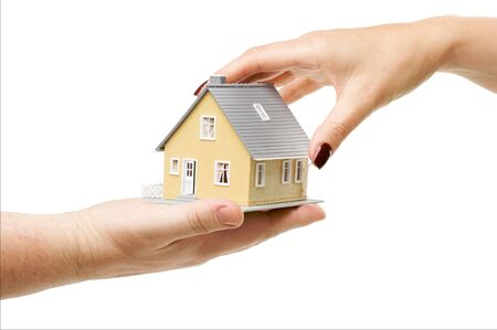 Female hand reaching for a house isolated on a white background. photo