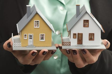 Female hands holding two houses. photo