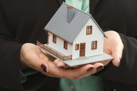 Female hands holding small house. photo