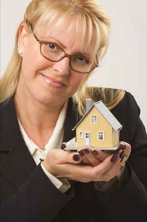 Female holding small house. photo