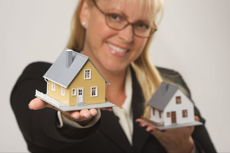 Female holding two houses and presenting one. photo