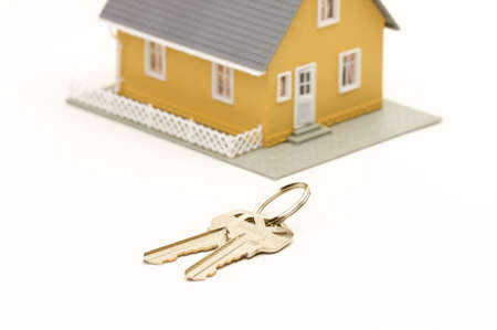 residencial: Keys and House isolated on a white background. Focus is on the keys. Stock Photo