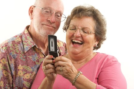 complementary: Senior Couple looks at the screen of a cell phone.