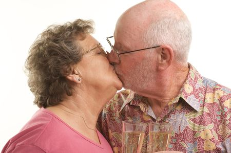 Happy Senior Couple kissing while holding Champagne glasses. photo