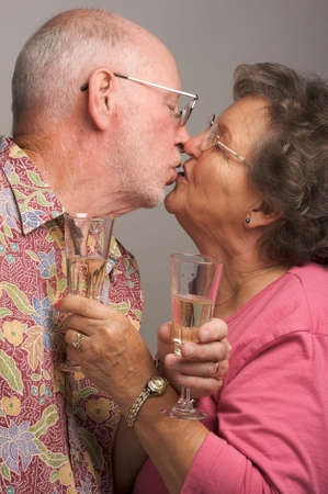 aging woman: Happy Senior Couple Kissing while holding Champagne glasses.
