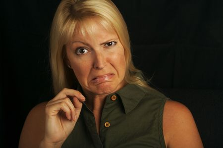 brown  eyed: Attractive Blond Haired, Brown Eyed Woman Grimaces on a black background. Stock Photo