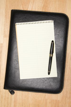 table surface: Pad of Paper, Pen & Leather Binder on a wooden background.