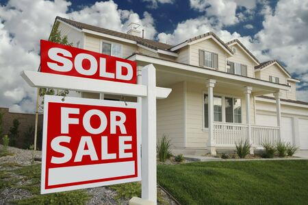 buying real estate: Sold Home For Sale Sign in Front of Beautiful New Home Stock Photo