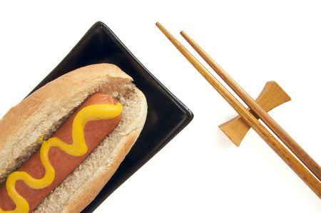 East Meets West - Hot Dog and Chopsticks Isolated on a White Background. Imagens