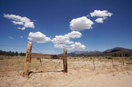 Puffy Storm Clouds Forming Over Field and Aged Fence on a blue sky. photo