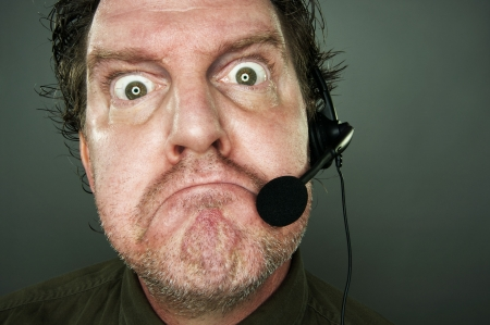 marketeer: Frowning man with telephone headset. Stock Photo