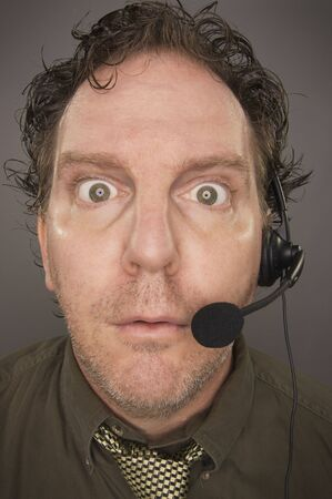 marketeer: Stunned Businessman Wearing Phone Headset Against a Grey Background.