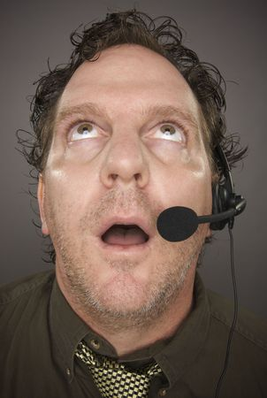 marketeer: Bewildered Businessman Wearing Phone Headset Against a Grey Background.