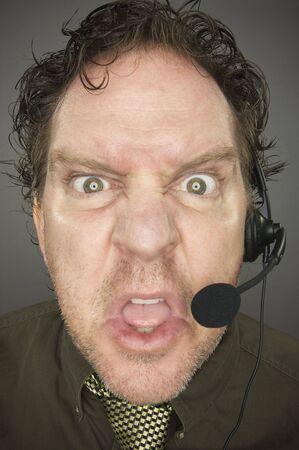 marketeer: Irate Businessman Wearing a Phone Headset Against a Grey Background. Stock Photo
