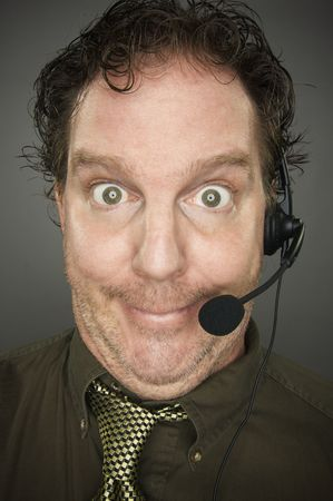 marketeer: Giddy Businessman Smiles Wearing a Phone Headset Against a Grey Background. Stock Photo