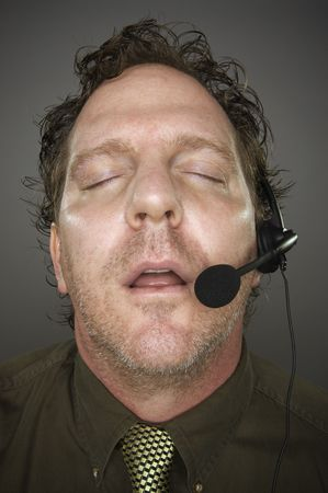 marketeer: Businessman Sleeps Wearing a Phone Headset Against a Grey Background.