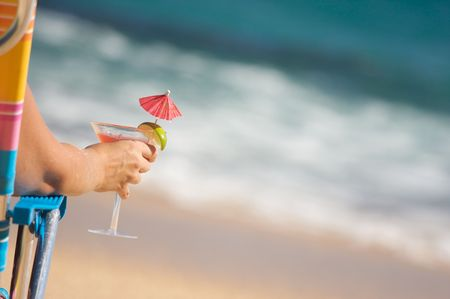 Woman Relaxing on Beach with Tropical Drink. photo