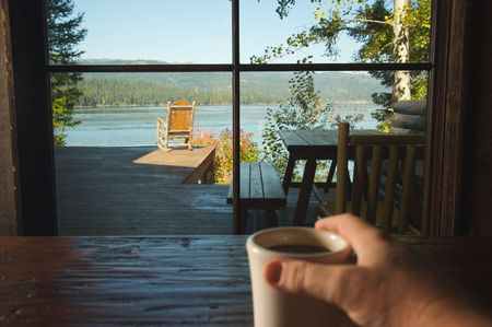 coffee table: Man Holds Cup of Coffee while enjoying View Of Lake Stock Photo