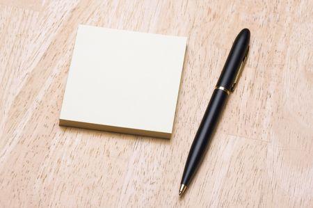 La pluma y el puesto que toma nota de la almohadilla contra un fondo de madera Foto de archivo - 3804153