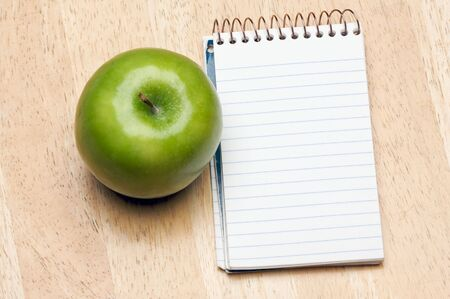 todo: Pad of Paper and Apple on a Wood Background Stock Photo