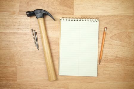 home improvement store: Pad of Paper, Pencil, Hammer and Nails on a Wood Background.