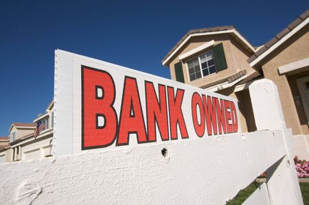 Bank Owned Real Estate Sign and House with American Flag in the Background. photo