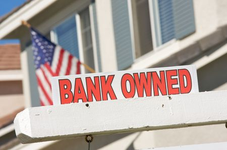 repossession: Bank Owned Real Estate Sign and House with American Flag in the Background.