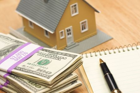 House and Money with Pad of Paper and Pen Stock Photo