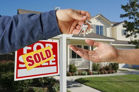 suburbia: Handing Over the Keys to A New Home with Sold Home For Sale Sign.