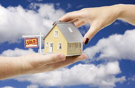 sold small: Per raggiungere una casa con Venduto Immobili Registrati su una Bright Blue Sky Contesto nuvoloso.