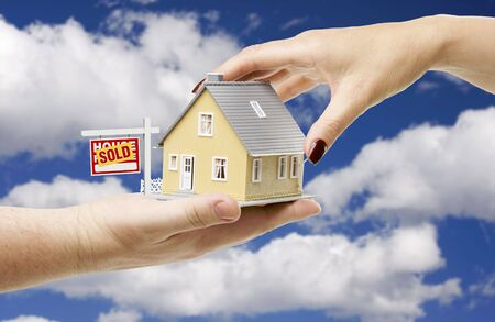 Reaching For A Home with Sold Real Estate Sign on a Bright Blue Cloudy Sky Background. photo