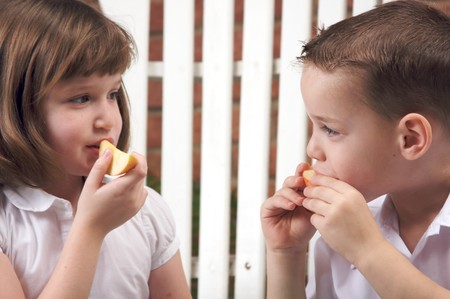 Sister and Brother Having Fun Eating an Apple photo