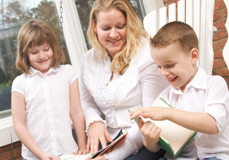 Young Boy Reads to His Mother and Sister Stock Photo - 4100259