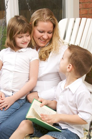 Young Boy Reads to His Mother and Sister photo
