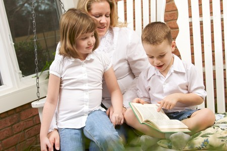Young Boy Reads to His Mother and Sister Stock Photo - 4100384