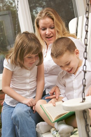 Young Boy Reads to His Mother and Sister Stock Photo - 4100419