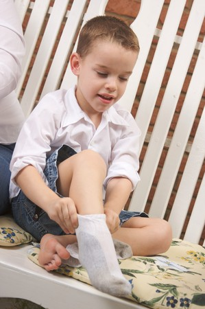 Adorable Young Boy Getting Dressed Putting His Socks On Stock Photo