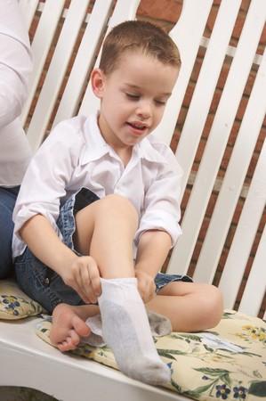 calcetines: Adorable Young Boy vestirse Poner En Su Calcetines