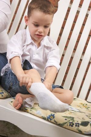 vistiendose: Adorable Young Boy vestirse Poner En Su Calcetines