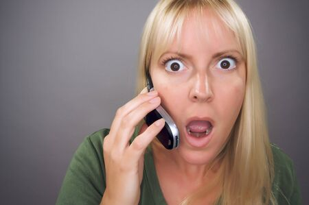 stunned: Stunned Blond Woman Using Cell Phone Against a Grey Background.