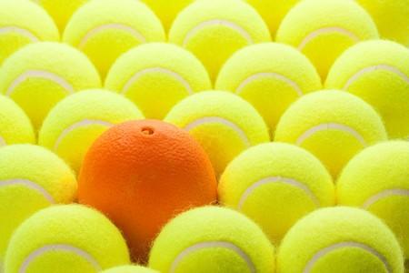 ornage: Macro Set of Brand New Tennis Balls and One Orange. Stock Photo