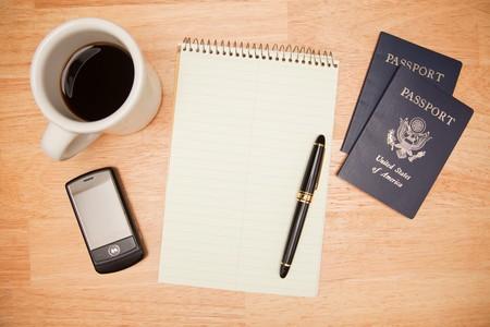 pad pen: Pad generales, Pen, Pasaportes, de caf� y de tel�fonos m�viles en un fondo de madera.