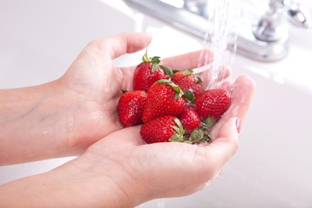 Woman Washing Strawberries in the Kitchen Sink. photo