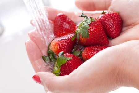 Woman Washing Strawberries in the Kitchen Sink. Stock Photo - 4331842