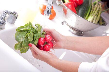wash basin: Woman Washing Radish in the Kitchen Sink.