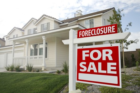Foreclosure Home For Sale Sign and House with Dramatic Sky Background. Stock Photo